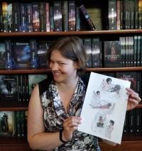 """Christina er forfatteren bag """"Sumpbaronens rejse"""". Her fremviser hun stolt et billede, som viser lidt af bogens handling (og meget af Robins bagdel)."""